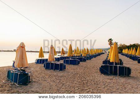 Yellow umbrellas and beach chairs at the at Aegean Sea beach. Start of season concept