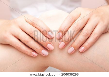 Young woman's knee joint being manipulated by osteopathic manual therapist or physician