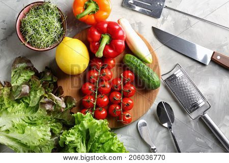 Wooden board with vegetables and utensils on kitchen table. Cooking classes concept
