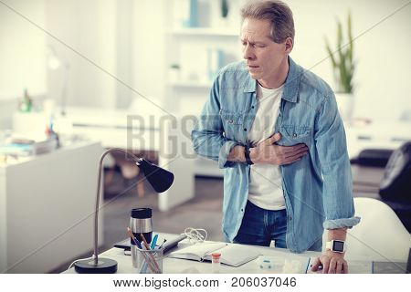 Risk of heart attack. Nice pleasant middle aged man standing in his office and holding his chest while feeling pain in the heart