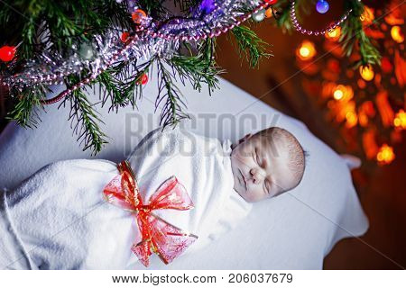 One week old newborn baby wrapped in blanket near Christmas tree with colorful garland lights on background. Closeup of cute child, little baby looking at the camera. Family, Xmas, birth, new life