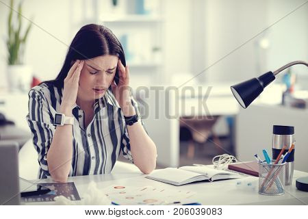 Strong headache. Unhappy cheerless beautiful woman sitting at the table and rubbing her temples while having a headache