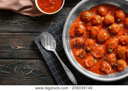 Saucepan with delicious meatballs in tomato sauce on table