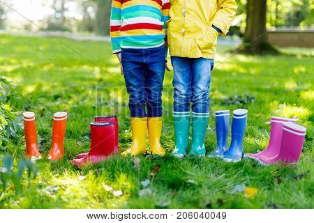 Little kids, boys or girls in jeans and yellow jacket in colorful rain boots. Close-up of children with different rubber boots. Footwear for rainy fall. Concept of bright autumn