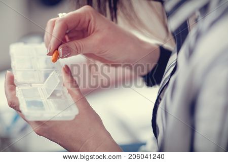 Medical treatment. Close up of a pill being taken out of the box by a nice beautiful pleasant woman while taking medicine