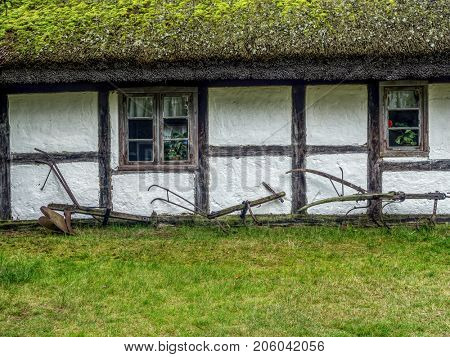 Old wooden farmstead with historical farming implements, part of heritage park in Kluki, Poland