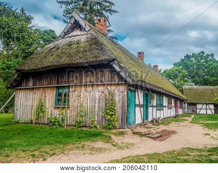 Old wooden farmstead with typical timber framing, part of heritage park in Kluki, Poland