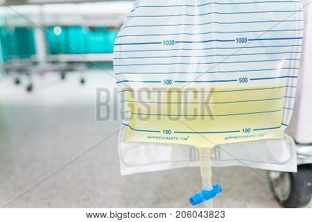 Urine bag hanging beside the patient's bed. Inside the hospital room.