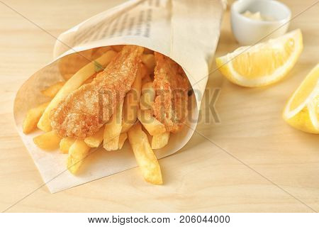 Tasty fried fish and potato chips rolled in paper on wooden table