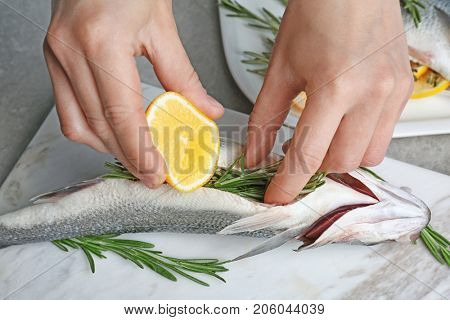 Woman squeezing lemon onto fish stuffed with rosemary on marble board, closeup