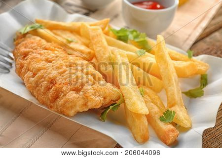 Paper plate with tasty fried fish and potato chips on table, closeup