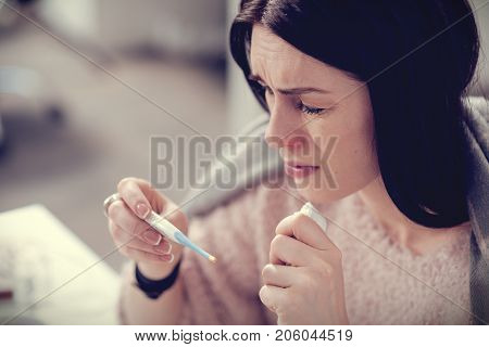 Serious disease. Cheerless sad unhappy woman looking at the thermometer and holding a paper tissue while having fever
