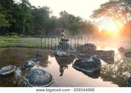 Young Asian woman practicing yoga pose in the park yoga and meditation have good benefits for health. Photo concept for Yoga Sport and Healthy lifestyle
