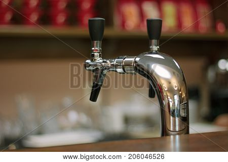 Metal beer tap on the bar whith the black handle