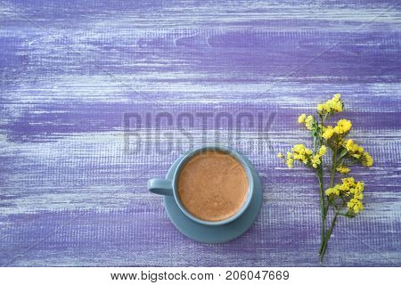Cup of aromatic morning coffee and flower on table