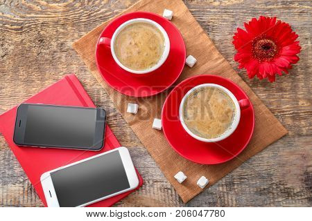 Cups of aromatic morning coffee and phones on table