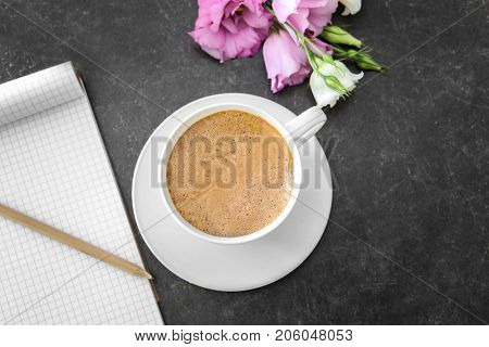 Cup of aromatic morning coffee and flowers on table