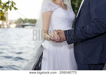 Groom in a blue suit holding the hand of a bride in a white dress on the embankment of the river couple newlyweds wedding 2 two couple together engagement ring