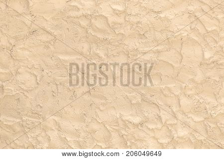 Beige surface made of the rough brushworks of plaster as a background