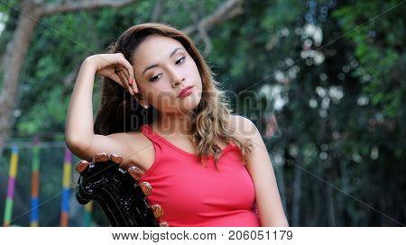 Sleepy Hispanic Female Sitting on a Park Bench