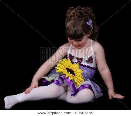 Doce menina com roupa de balé roxo e branco sentado a olhar