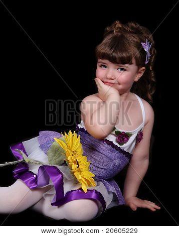 Doce menina com roupa de balé roxo e branco sentado com
