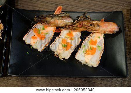 Fresh shrimps topping with shrimp egg on black plate