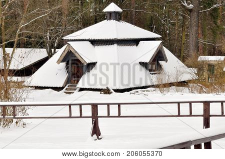 Old wooden barn covered with snow at the forest's edge