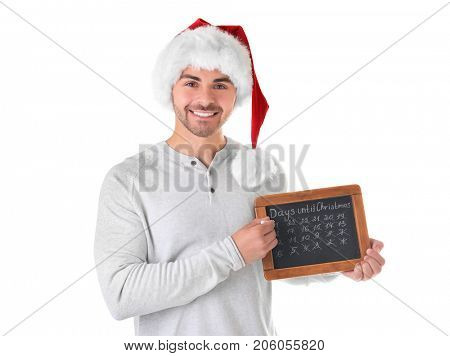 Young man in Santa hat with chalkboard counting days until Christmas, on white background