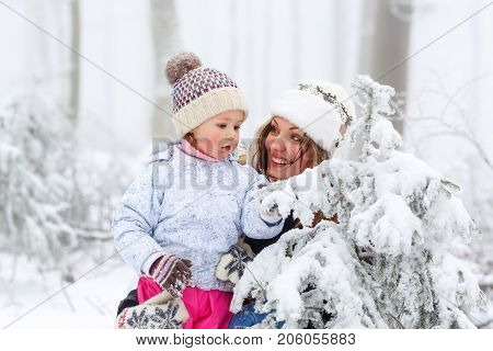 happy family with young mother and child daughter on a winter walk outdoors. Kid toddler girl and beautiful woman having fun in snow forest. Family of two playinig on snowy frosty winter day.