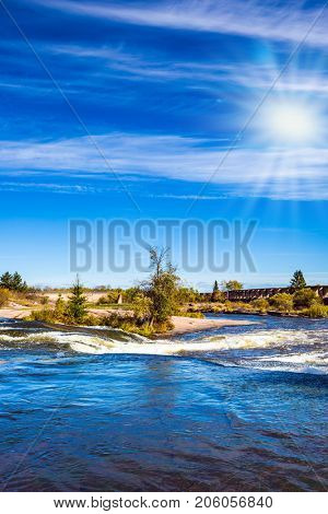 The concept of recreational and ecological tourism. Indian summer in Manitoba, Canada. Plumose clouds and autumn sun over the river Winnipeg