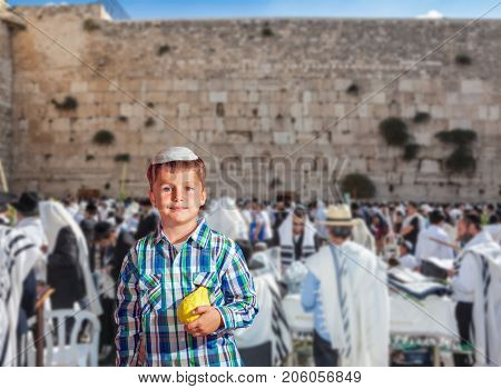 Beautiful Jewish boy in white skullcap, with etrog. The greatest shrine of Judaism is the Western Wall of the Temple. Autumn Jewish holiday Sukkot