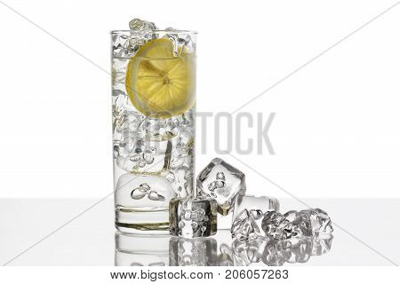 glass full of fresh water with lemon slice and ice cubes on background