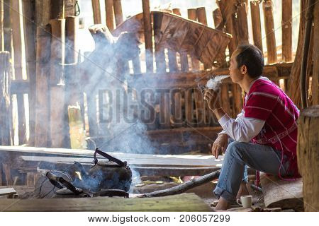 MAE KLANG LUANG, THAILAND, FEBRUARY 2, 2017 : A Karen tribe man is sitting and smoking a cigarette, waiting for the tea water to boil in the village of Mae Klang luang near Chiang Mai, Thailand