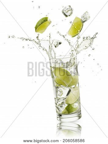glass full of water with lime slices and ice cubes falling and splashing water on white background
