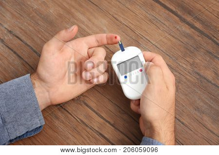 Hands of man using digital glucometer on wooden background. Diabetes concept