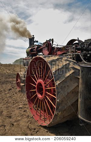 Amish steam tractor engine plowing the field