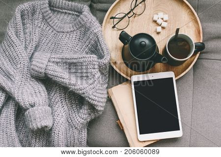 Cashmere sweater, reading and serving tray on gray sofa. Warm weekend at home. Detail of cozy winter interior. Watching movies on tablet pc.
