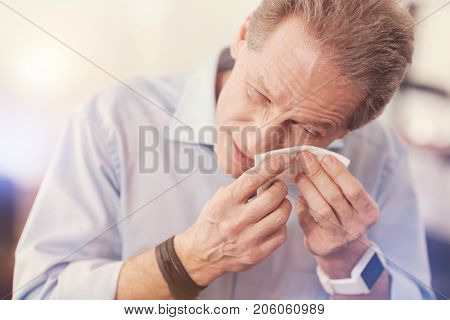 It hinders me. Cheerless man getting an eyewinker from his eye and using a tissue while standing in the office
