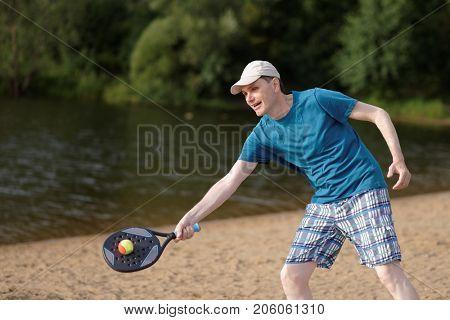 Man playing beach tennis on a beach