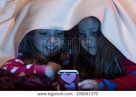 Girl Friends Under Blanket Playing With Mobile Phone