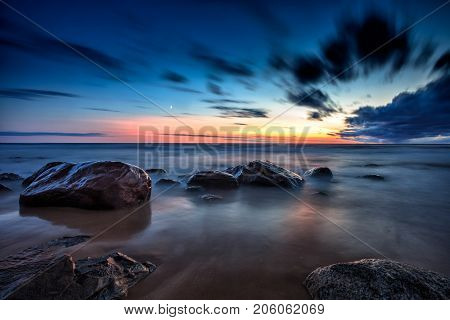 Baltic Sea sunset seascape with wet rocks. Smooth long exposure of waves