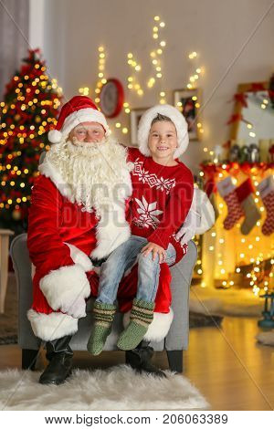 Happy little boy sitting on Santa's lap in room with beautiful Christmas decorations
