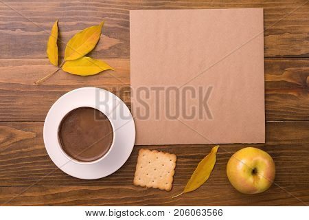 Autumn composition with coffee, leaves, apple, paint brush and cookies on a wooden table.