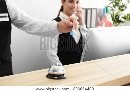 Hand of male receptionist with room key in hotel
