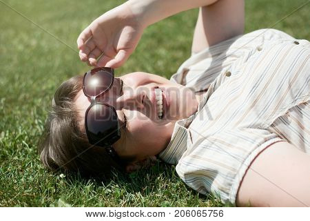 Woman lie on green grass and squint from the bright sun, summer outdoor