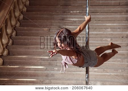 Beautiful brunette dancing on a pole on underground background.