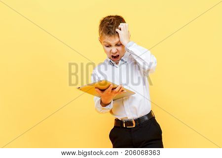 Little boy in formal clothing looking terrified while holding tablet and posing on orange background.