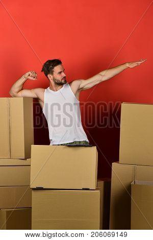 Man Pretending To Fly Like Superhero Among Cardboard Boxes