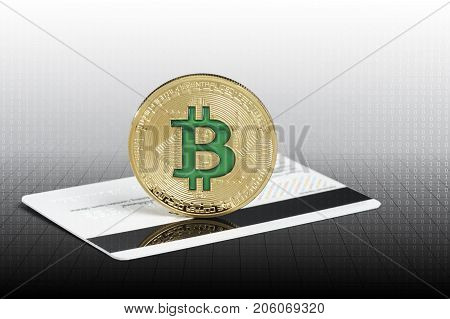 Cryptocurrency physical green bitcoin coin over the credit card.